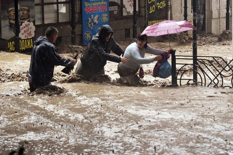 Ялта, Россия. Люди пытаются перейти через затопленную улицу в центре города