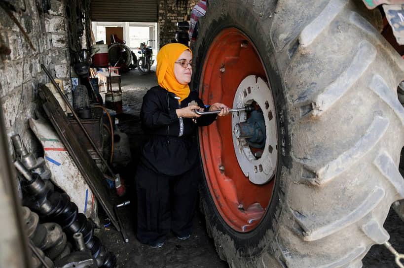 Кафр-эш-Шейх, Египет. Механик ремонтирует колесо трактора в гараже