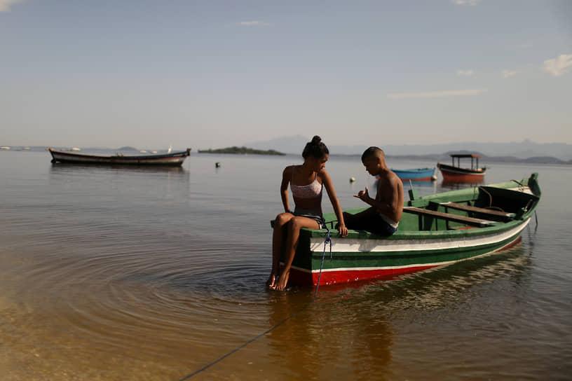 Рио-де-Жанейро, Бразилия. Местные жители отдыхают в лодке на пляже