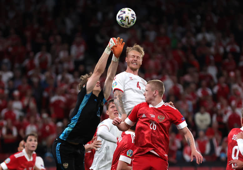 Датчанин Симон Кьер (в центре) в борьбе за мяч с российским вратарем Матвеем Сафоновым