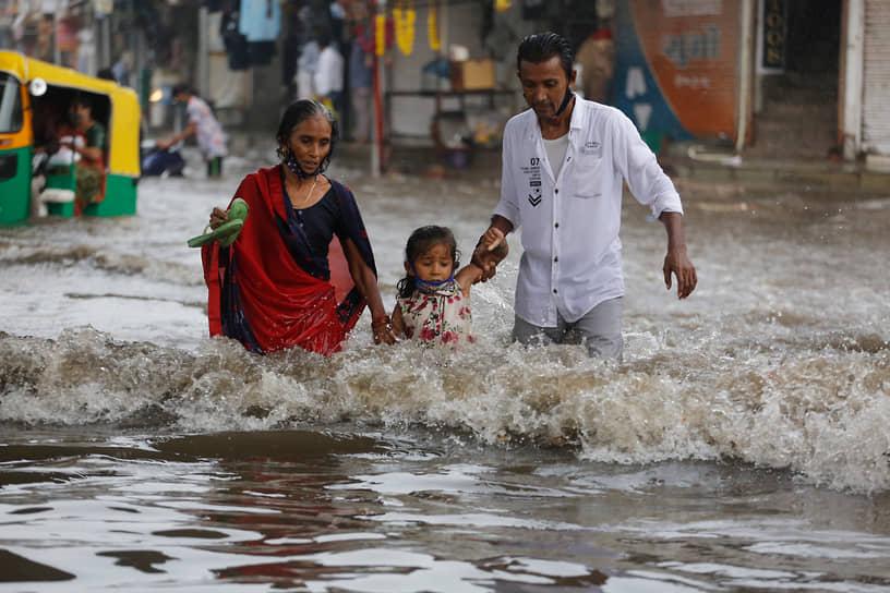 Ахмедабад, Индия. Семья идет по затопленной дороге