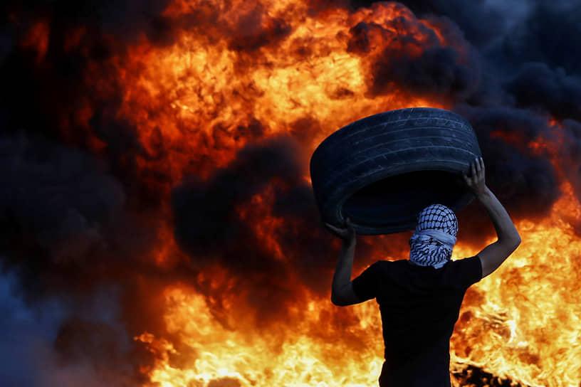 Бейта, Западный берег реки Иордан. Палестинский демонстрант несет шину