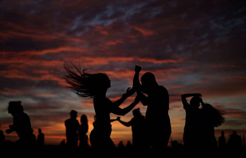 Копенгаген, Дания. Люди танцуют на фоне заката