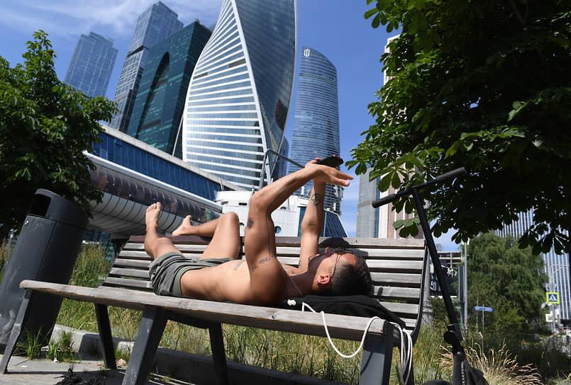 Мужчина отдыхает на лавочке на Пресненской набережной в Москве