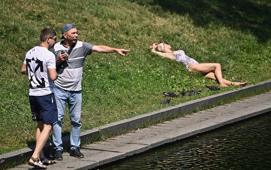 Люди отдыхают на берегу пруда в Москве