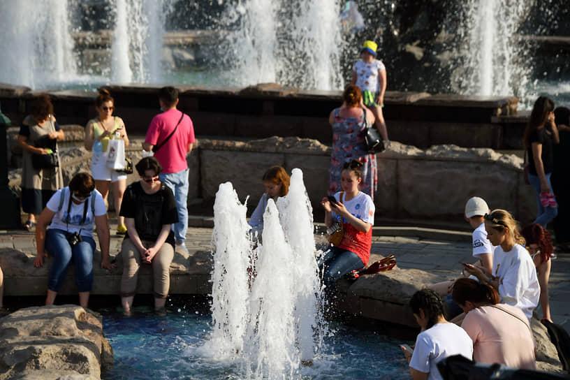 Отдыхающие у фонтана в Александровском саду в Москве