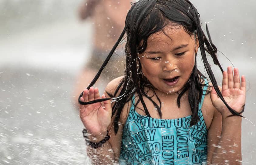 Девочка купается в фонтане парка имени 300-летия Санкт-Петербурга