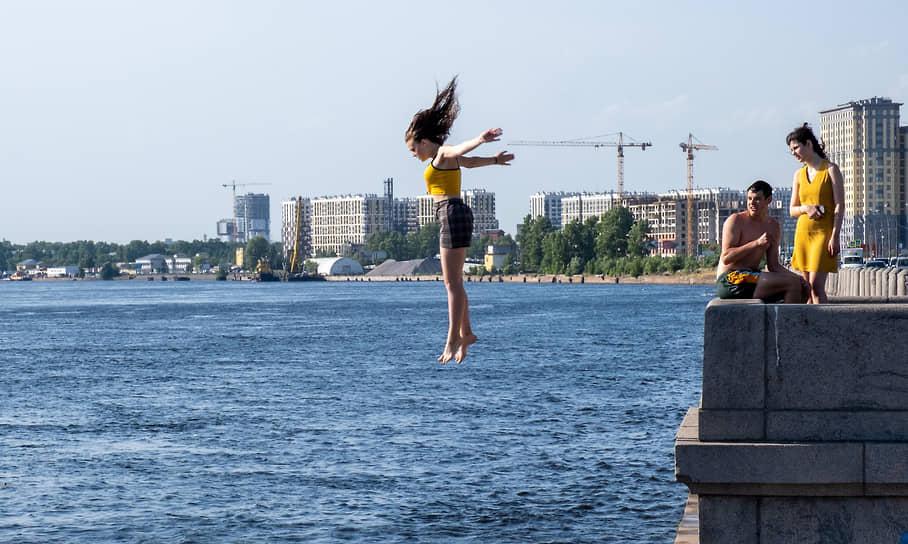 Девушка прыгает в реку Нева в Санкт-Петербурге