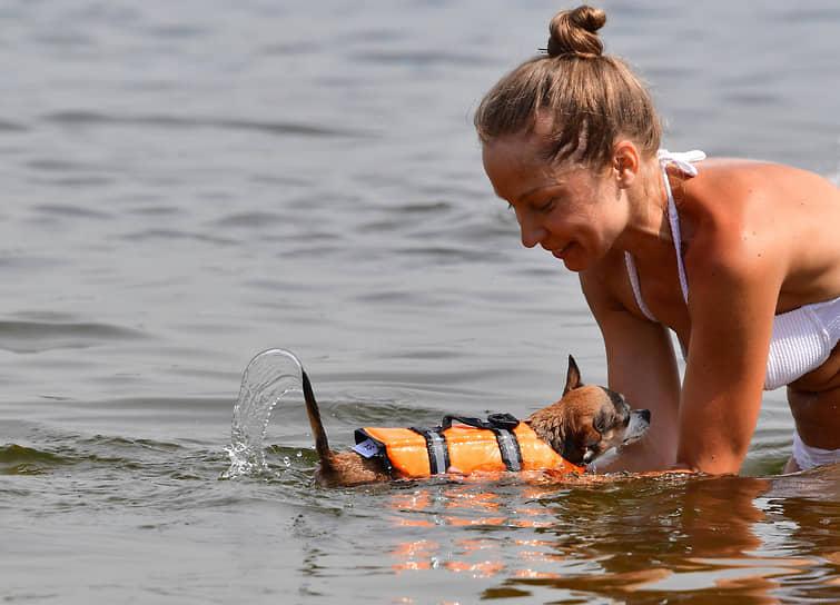 Девушка с собакой на пляже в московском районе Строгино