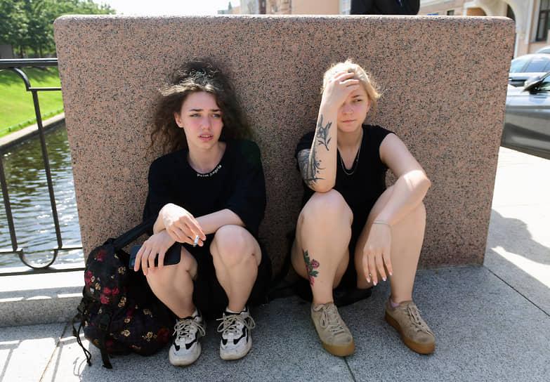 Девушки сидят у Адмиралтейского канала в Санкт-Петербурге