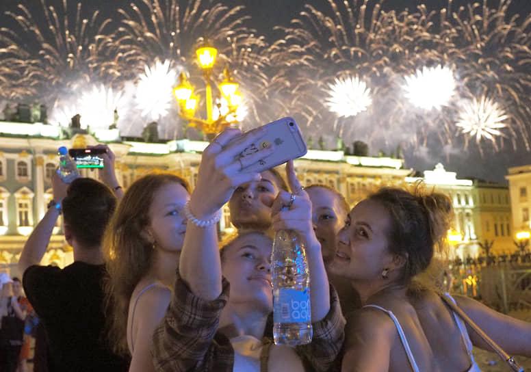 Выпускники на Дворцовой площади во время праздничного фейерверка