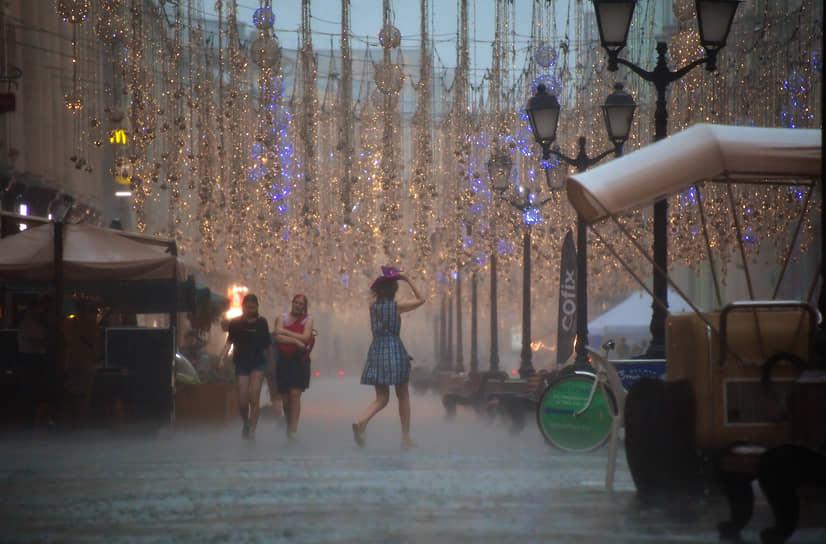 Люди идут под проливным дождем в центре Москвы