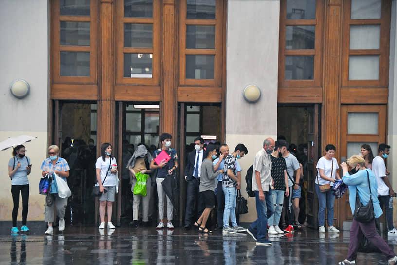 Люди укрываются от дождя возле станции метро