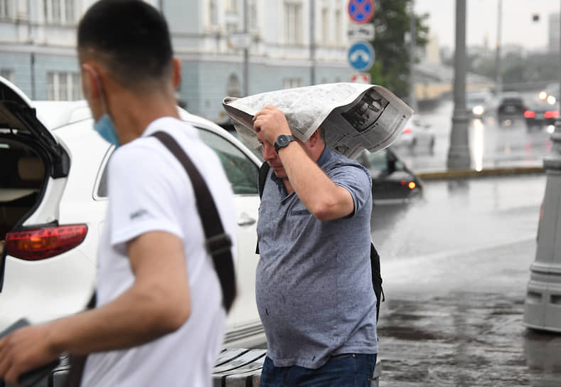 Мужчина укрывается газетой в центре города