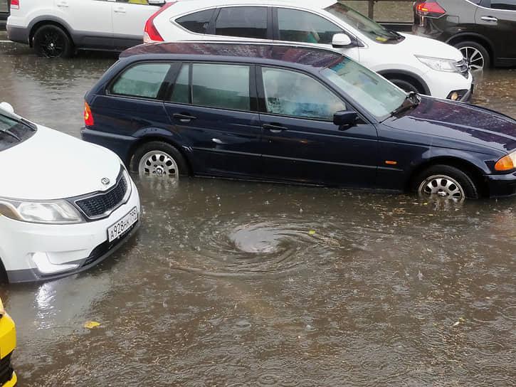 Водители пытаются проехать по затопленной дороге в районе Беляево