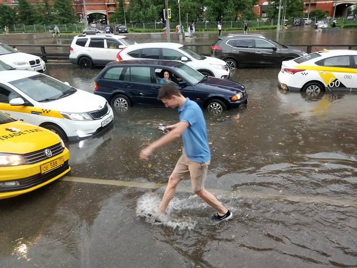Молодой человек пытается перейти через затопленную дорогу