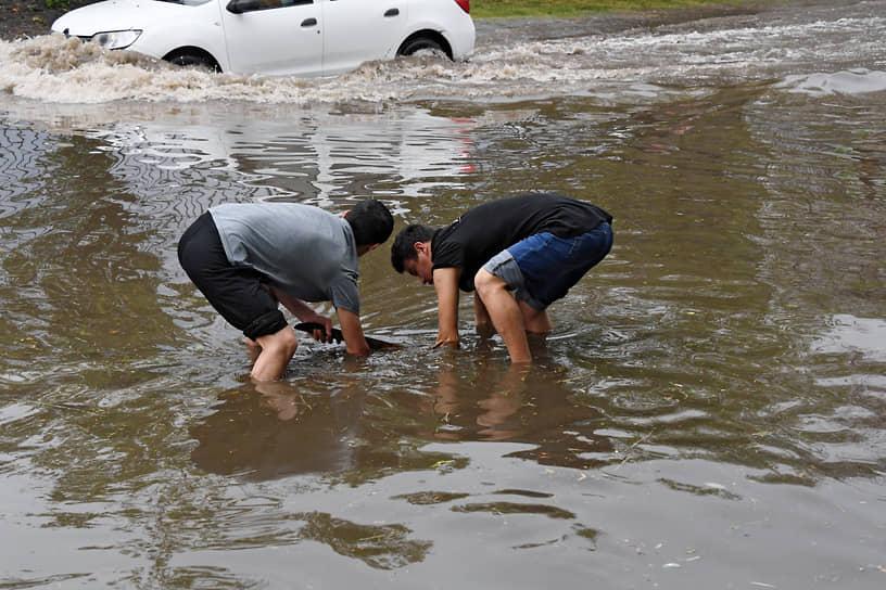Мужчины пытаются открыть канализационный люк в районе Ясенево