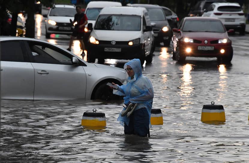 Женщина посередине затопленной дороги