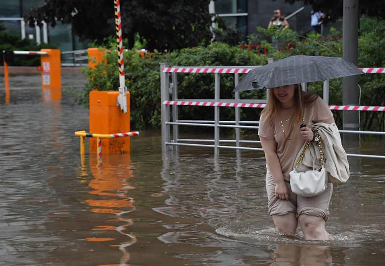 Женщина переходит затопленную из-за сильного дождя дорогу