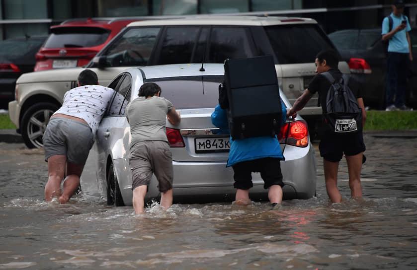 Люди толкают машину на дороге по колено в воде