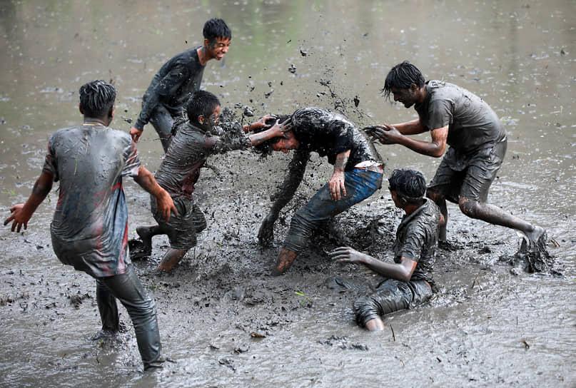 Бхактапур, Непал. Люди играют в грязи во время фестиваля