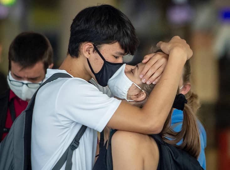 Влюбленные в масках в аэропорту Франкфурта, Германия
