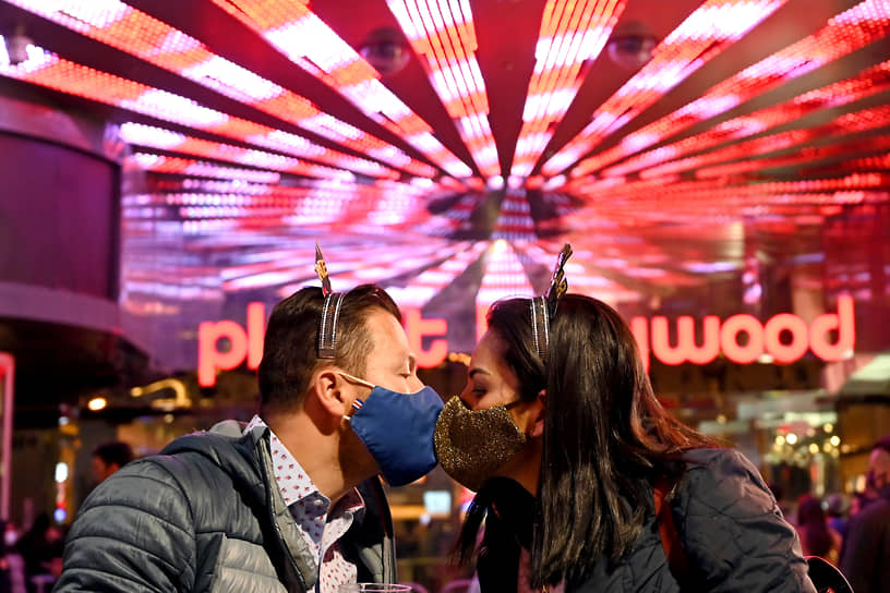 Пара в масках целуется в Лас-Вегасе во время празднования Нового года