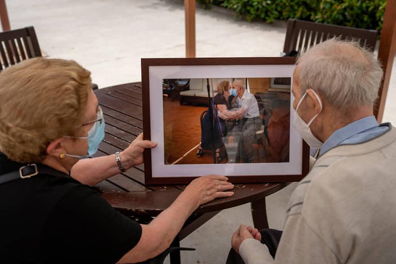 Пожилая пара рассматривает фотографию, удостоенную Пулитцеровской премии, на которой они целуются вместе в доме престарелых в Барселоне