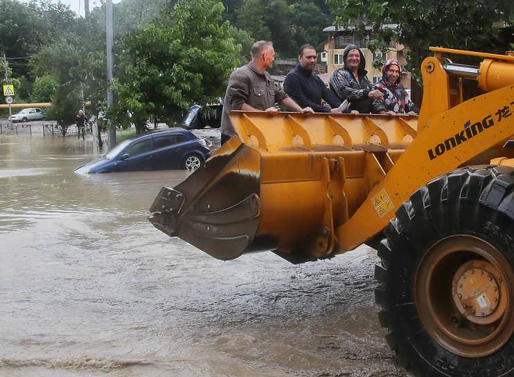 Во время сильных дождей в море попало большое количество мусора<br> На фото: рабочие возле автомобиля на затопленной улице в микрорайоне Кудепста