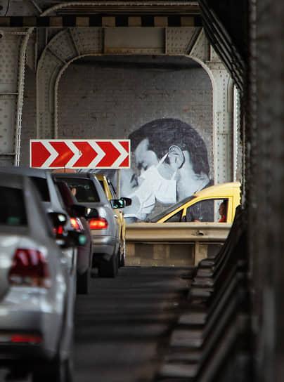 Граффити на опоре двухъярусного моста с изображением целующейся пары в медицинских масках, Калининград