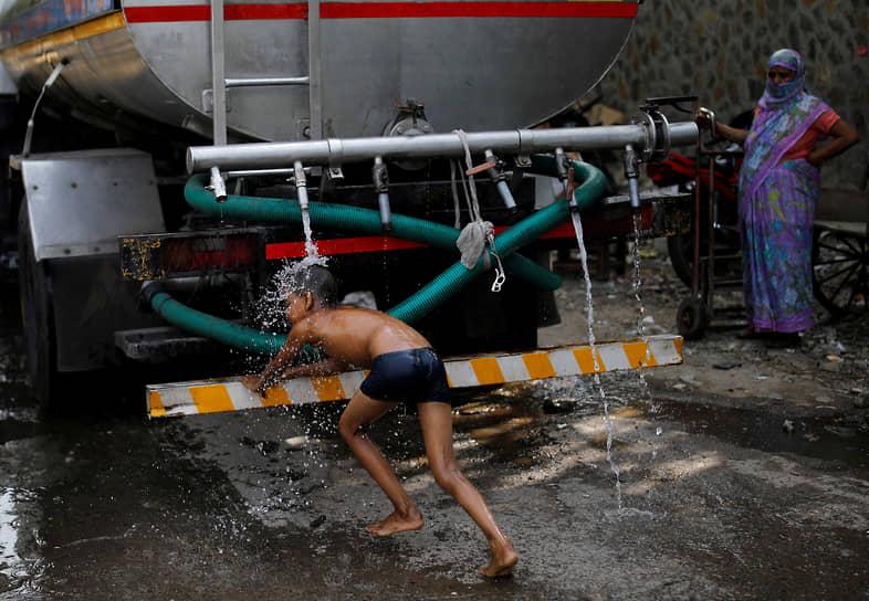 Нью-Дели, Индия. Мальчик умывается под краном городской автоцистерны