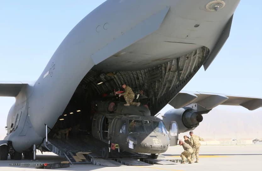 Уход из Афганистана был одним из предвыборных обещаний Джо Байдена. Объясняя это решение, он заявлял, что «только народ Афганистана имеет право и обязанность руководить своей страной, а бесконечные американские войска не могут ни создать, ни поддерживать устойчивое афганское правительство». 8 июня Пентагон заявил о выводе 50% американского контингента <br>На фото: погрузка вертолета UH-60L Blackhawk для его транспортировки обратно в США