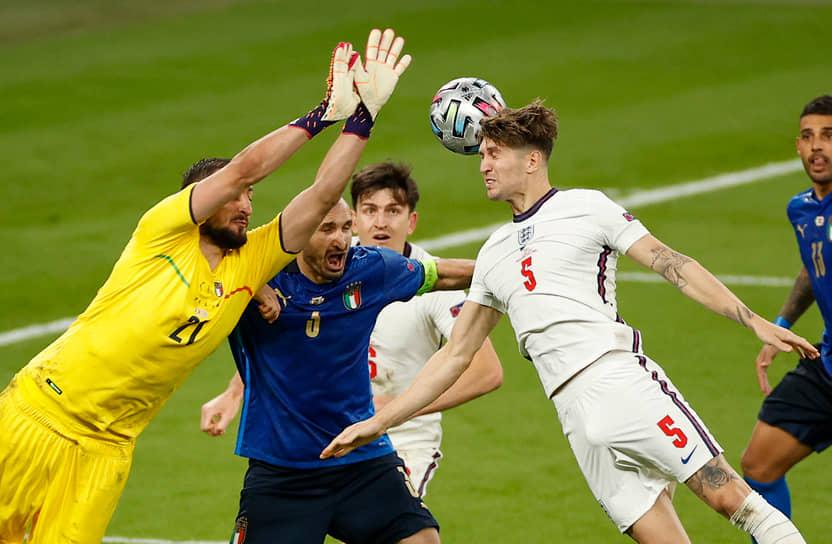 Итальянский голкипер Джанлуиджи Доннарумма (слева) в борьбе за мяч с английским защитником Джоном Стоунзом