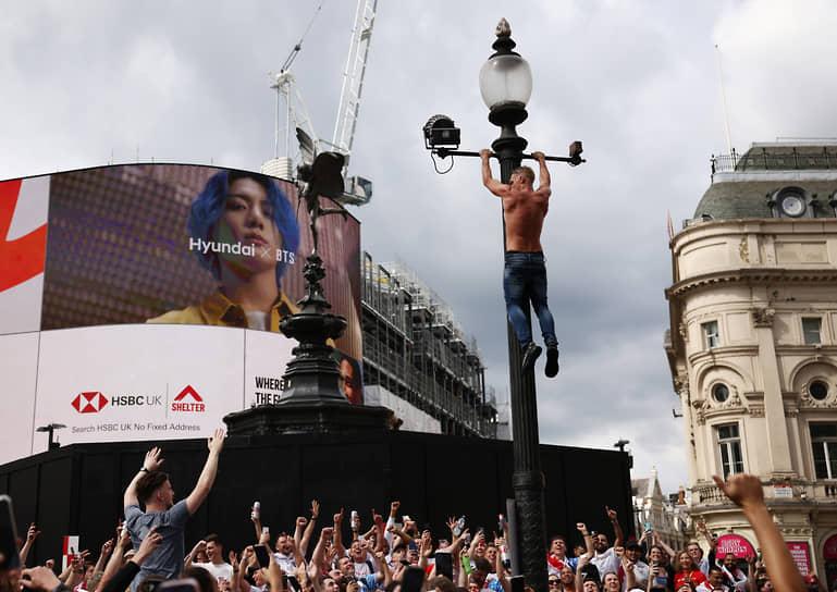 Фанат повис на фонарном столбе на площади Пикадилли в центре Лондона в преддверии финального матча Евро-2020