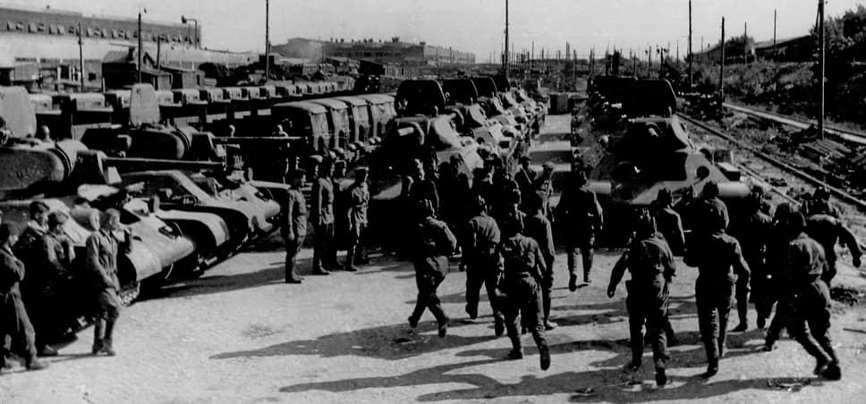 Производство танков Т-26 в спеццехах СТЗ начали налаживать в 1932 году, когда были разорваны контракты с американскими специалистами. Всего в Сталинграде было выпущено около 200 машин Т-26. В 1940 году началось производство танков Т-34. После потери Харьковского тракторного завода во время войны СТЗ стал главным поставщиком «тридцатьчетверок» в армию, выпуская по 200–300 танков в месяц<br> На фото: танкисты получают боевые машины на тракторном заводе и сразу отправляются в бой в августе 1942-го