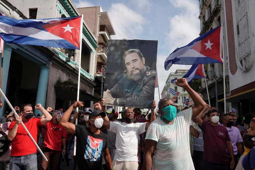 Сторонники правительства держат фотографию покойного кубинского лидера Фиделя Кастро