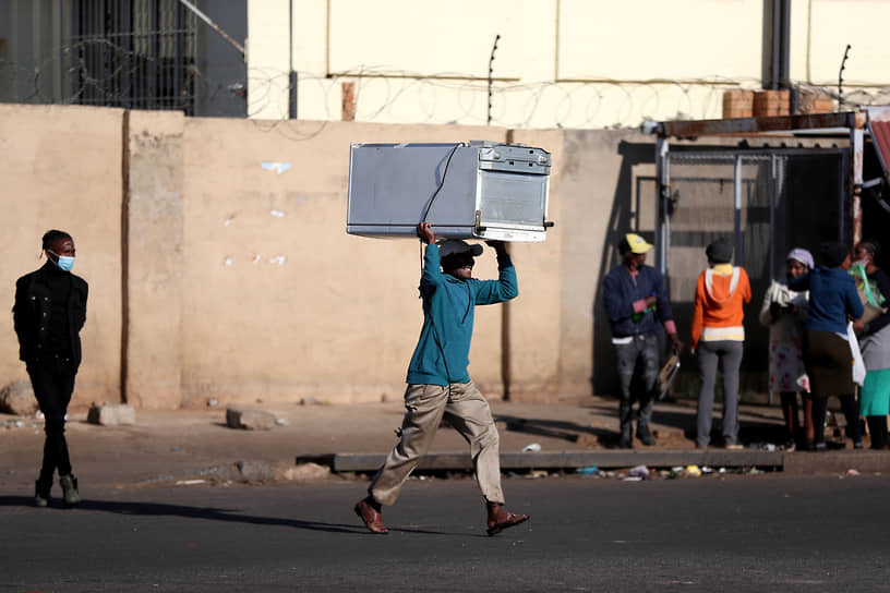 Катлехонг, ЮАР. Мужчина во время разграбления торгового центра в ходе беспорядков в знак протеста против заключения экс-президента страны Джейкоба Зумы