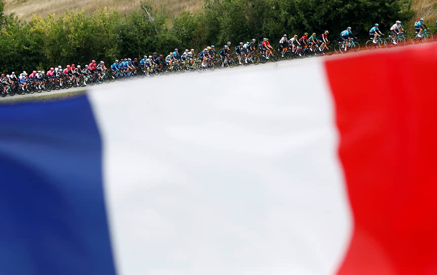 Франция. Участники велогонки «Тур де Франс» на фоне национального флага