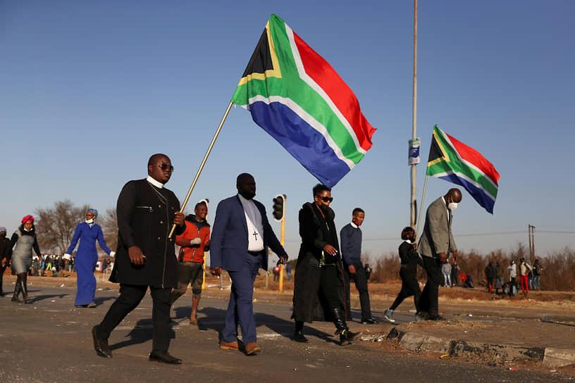 Религиозные лидеры с флагами ЮАР проходят возле разграбленного торгового центра