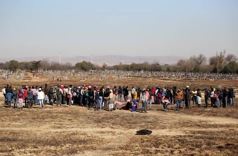 Местные жители и члены семьи собираются возле тела 15-летнего Вуси Дламини, застреленного во время беспорядков