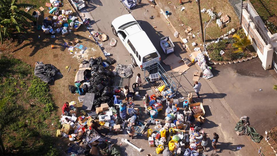 Люди грабят территорию возле горящего склада в ЮАР
