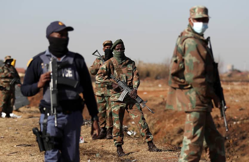 Сотрудники службы безопасности ЮАР патрулируют улицы во время беспорядков