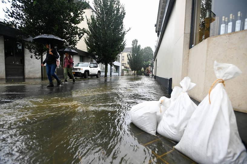 Люди идут по затопленной улице в Нидерландах