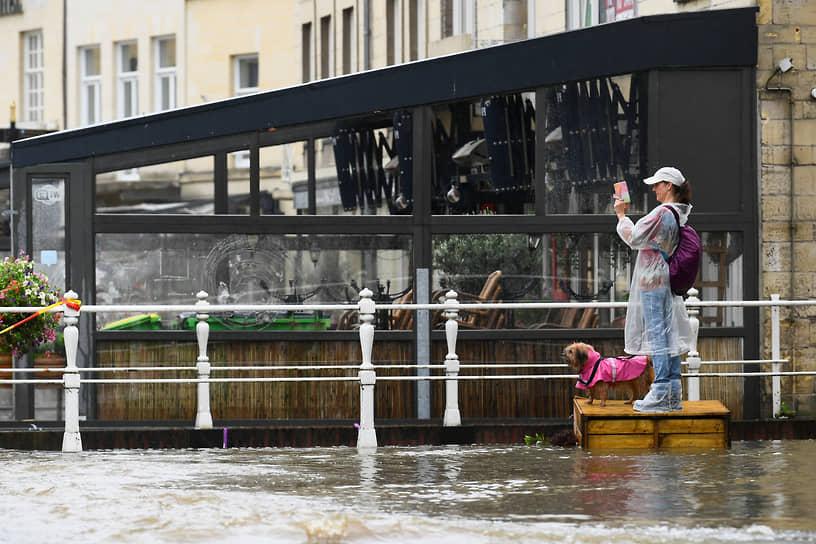 Женщина фотографирует затопленную улицу в Нидерландах