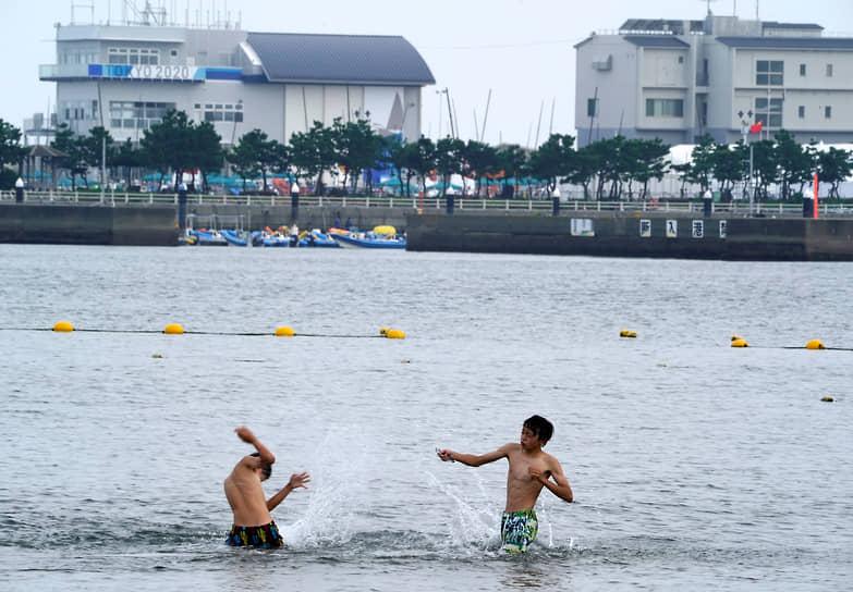 Молодые люди купаются неподалеку от места проведения соревнований по парусному спорту