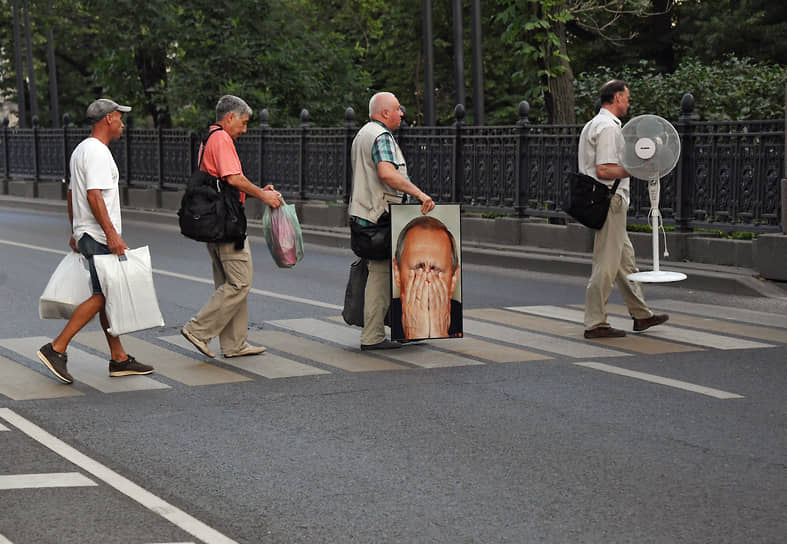 Москва, Россия. Мужчины идут через дорогу по пешеходному переходу в центре города