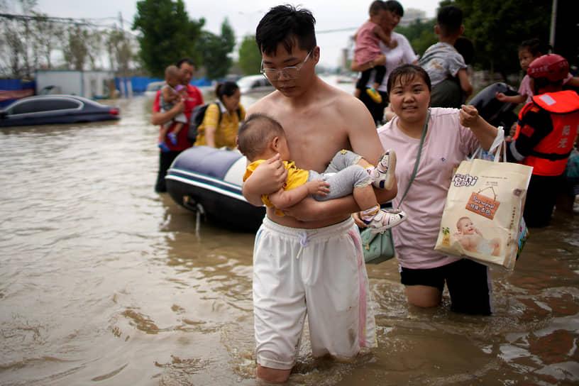 Чжэнчжоу, Китай. Мужчина идет с ребенком на руках по затопленной улице