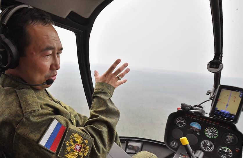 Республика Саха (Якутия), Россия. Глава Республики Саха Айсен Николаев в кабине вертолета во время инспекции тушения пожаров