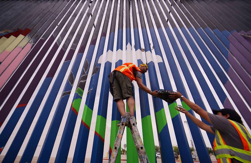 Мехикали, Мексика. Активисты рисуют граффити на стене, отделяющей республику от США