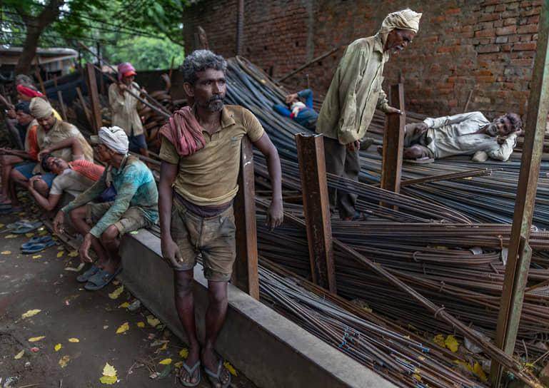 Праяградж, Индия. Рабочие при перевозке железных прутьев, используемых при строительстве зданий